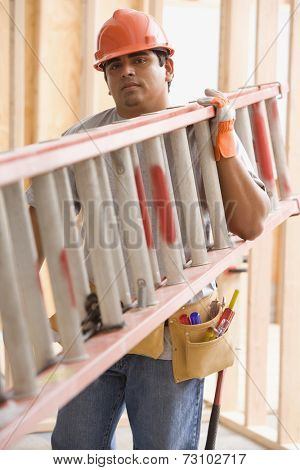 Portrait of construction worker carrying ladder on shoulder