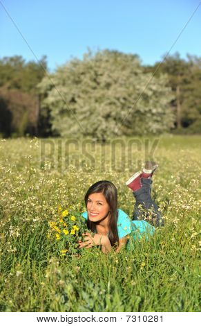 Beautiful Young Woman Lying In Blooming Meadow