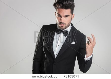 Close up picture of a handsome young man in tuxedo snapping his finger while looking at the camera
