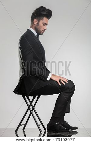 Side view of an elegant young man sitting on a stool looking down. On grey studio brackground.