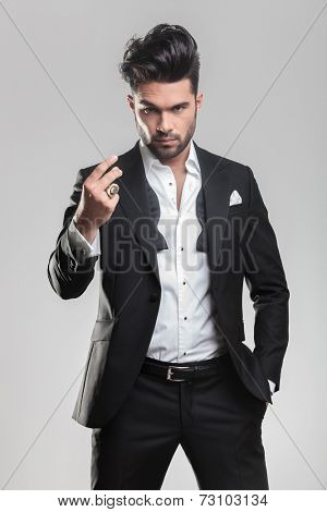 Elegant young man in tuxedo looking at the camera while snapping his finger and holding one hand in his pocket.