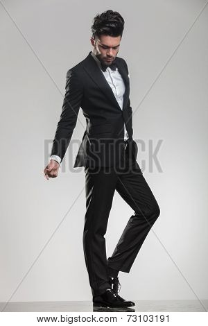 Young man in tuxedo looking down while snapping his finger, full body picture.