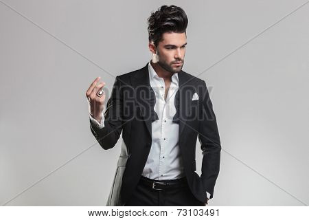 Handsome young man in tuxedo snapping his finger while looking away from the camera. On grey background.