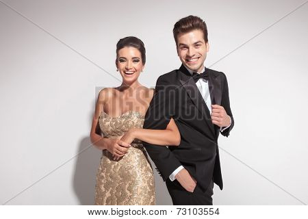 Elegant couple laughing for the camera while holding arm to arm. On grey background.