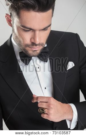 Close up picture of an elegant young man in tuxedo looking down, thinking.