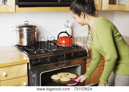 Young woman taking food out of the oven