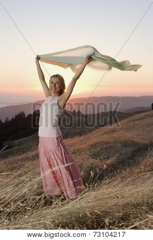Senior woman holding her sweater into the wind