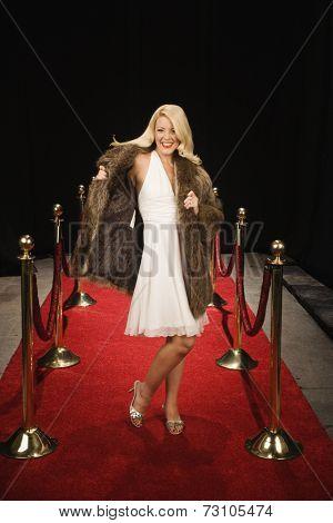 Female celebrity walking down empty red carpet