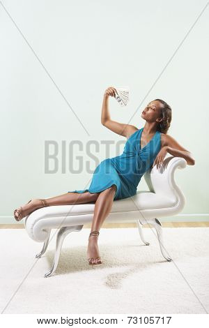 Young woman fanning herself with cash
