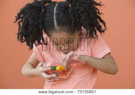 Asian girl with ponytails looking in bowl of candy