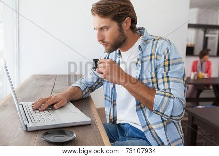Casual man using laptop drinking espresso at the coffee shop