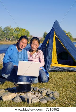 Mongolian sisters using a laptop while camping.