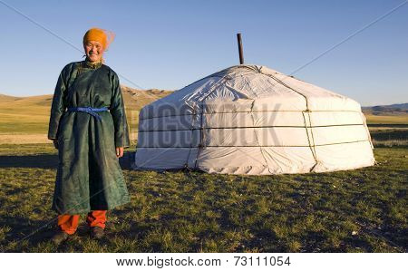 Mongolian woman standing in front of the tent outdoors.