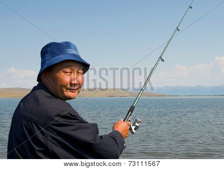 Mongolian man fishing in one of many Mongolia lakes.