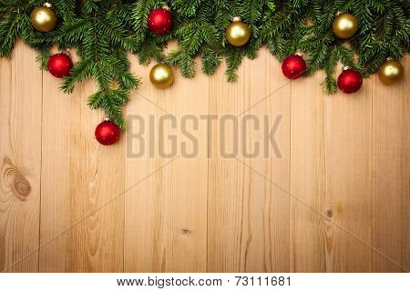 Christmas background with fresh fir-tree and  baubles on wood - horizontal