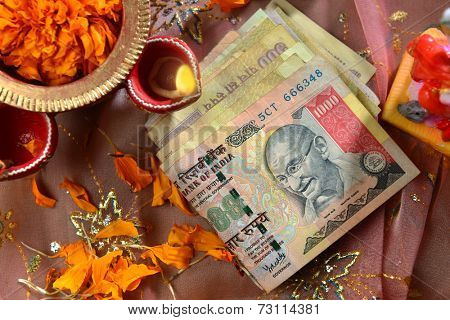 Indian currency bills with traditional lamp - a top angle view