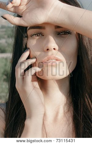 Seductive sensual young woman with long brunette hair and her arm raised to her forehead looking at the camera with a sultry sexy expression and parted lips