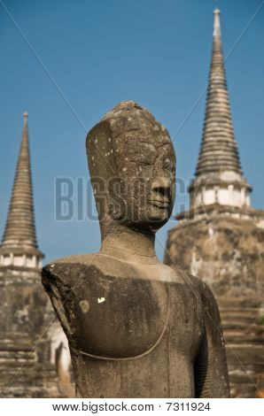 Stupa (chedi) Of A Wat In Ayutthaya, Thailand, With Buddha Staue. The Statue Is Incomplete