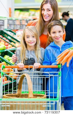 Family selecting fruits and vegetables while grocery shopping in supermarket