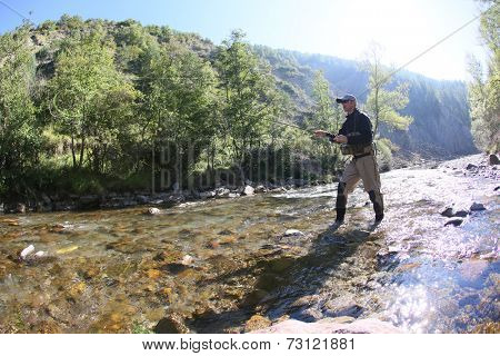Fisherman using flyfishing rod in beautiful river