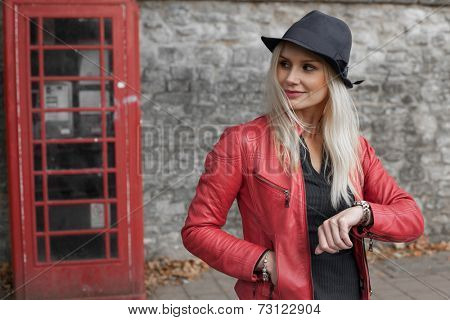 Stylish young blond woman in a red leather jacket and hat standing waiting outside a red telephone kiosk checking her watch and looking down the street