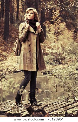 Happy young fashion woman with handbag in autumn forest