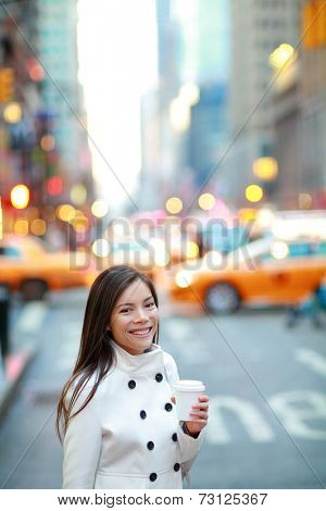 Young casual urban professional business woman in New York City Manhattan drinking coffee walking in street wearing coat downtown with yellow taxi cabs in background.