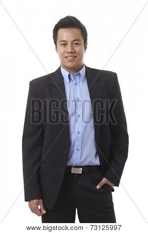 Portrait of smiling, young, Asian businessman standing hand in pocket.
