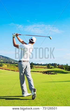 Man Playing Golf on Beautiful Sunny Green Golf Course. Hitting Golf Ball down the Fairway.