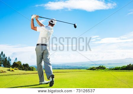 Man Playing Golf on Beautiful Sunny Green Golf Course. Hitting Golf Ball down the Fairway from the Tee with Driver.