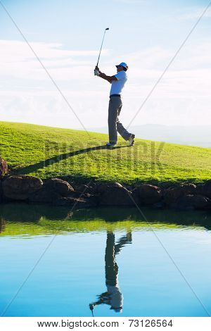 Silhouette of Man Playing Golf on Beautiful Course, Reflection in Water