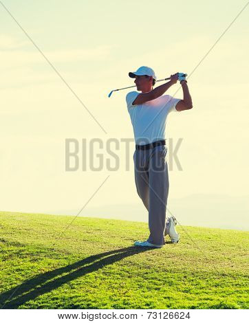 Man Playing Golf on Course Early Morning at Sunrise