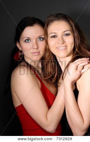 zwei junge Lesben Mädchen Freund auf grauem Hintergrund