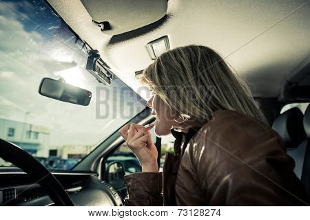 Female driver doing makeup in her car