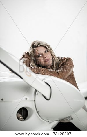 A woman pilot standing next to airplane, looking at camera