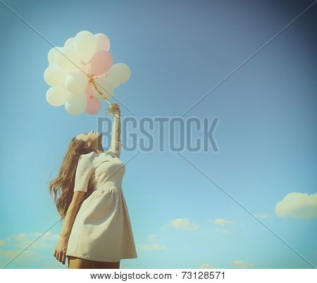 Fashion girl with  air balloons over blue sky, toned.