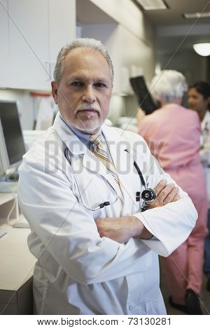 Middle-aged male doctor with arms crossed