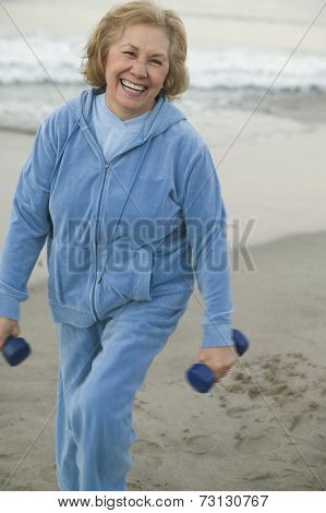 Senior woman with weights at the beach