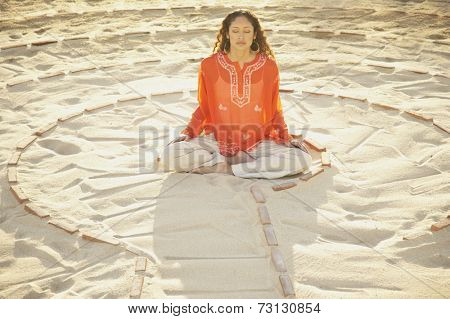 Woman sitting cross-legged in the middle of a meditation labyrinth