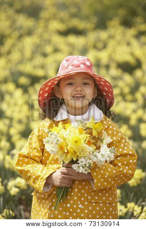 Young Hispanic girl in rain gear with flower bouquet outdoors