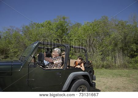 Hispanic family riding in jeep