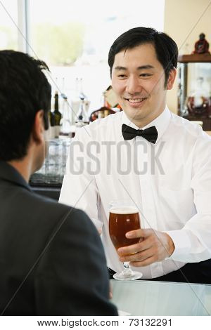 Asian male bartender serving man drink at bar