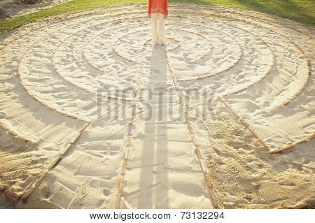 Person standing in the middle of a meditation labyrinth