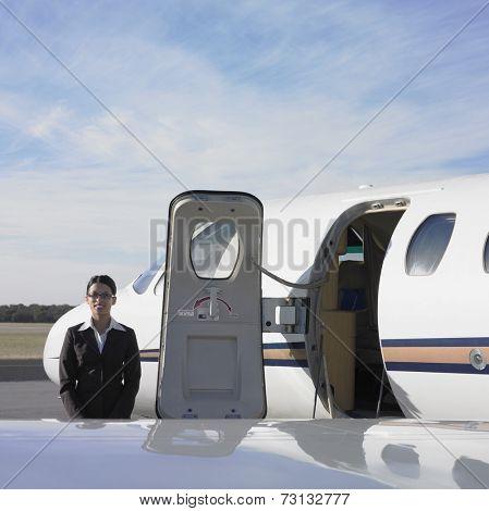 Female flight attendant next to airplane door