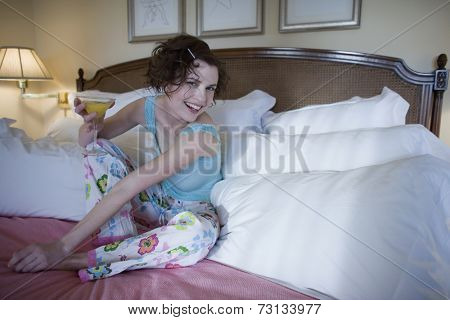 Woman sitting on bed with cocktail