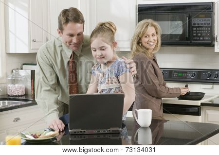 Family making breakfast and looking at laptop