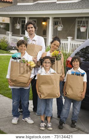 Hispanic family unloading grocery bags from car