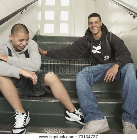 Two young men laughing on stairs at school