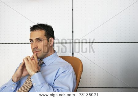 Businessman sitting in chair thinking