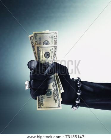 Woman's gloved and jeweled hand crushing US hundred dollar bills
